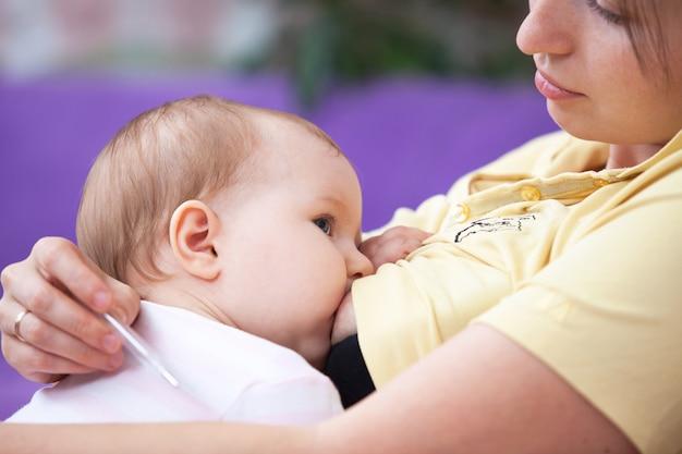 Una giovane donna allatta un bambino e ne misura la temperatura Foto Premium