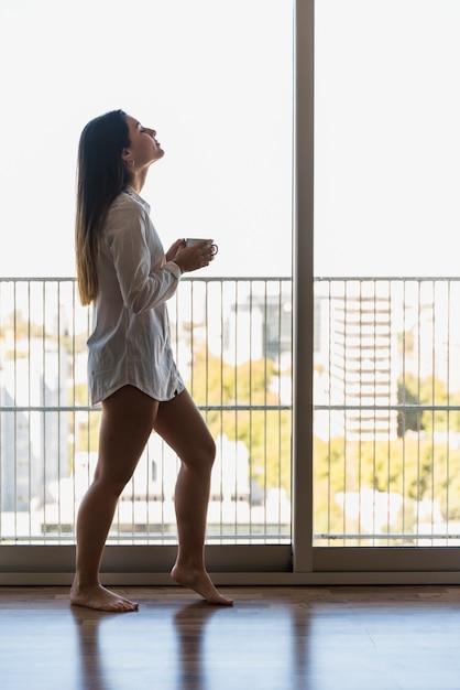 Una giovane donna attraente in balcone tenendo la tazza di caffè al mattino Foto Gratuite