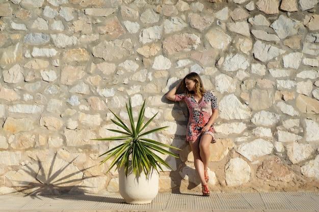 Una giovane donna bellissima in un abito corto cammina per le strade di una piccola città europea. Foto Gratuite