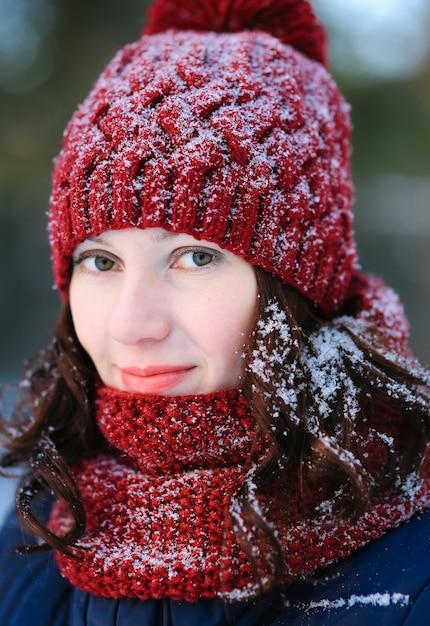 Una giovane donna cammina in un parco d'inverno in una calda sciarpa rossa e cappello. Foto Premium