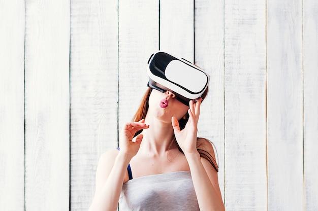 Una giovane donna che indossa occhiali vr, tenendo le mani in faccia, sfondo bianco in legno Foto Premium