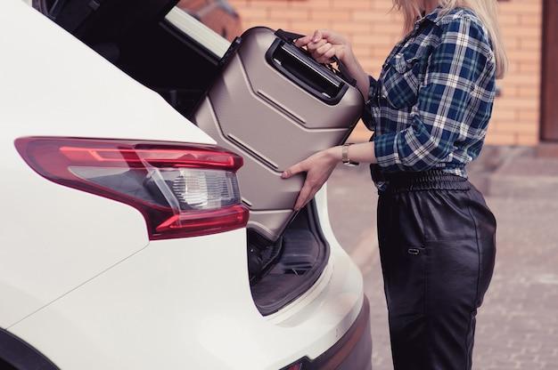 Una giovane donna che mette i suoi bagagli nel bagagliaio di un'auto Foto Premium