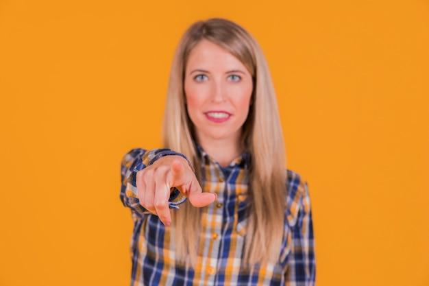 Una giovane donna che punta il dito verso la fotocamera contro uno sfondo arancione Foto Gratuite