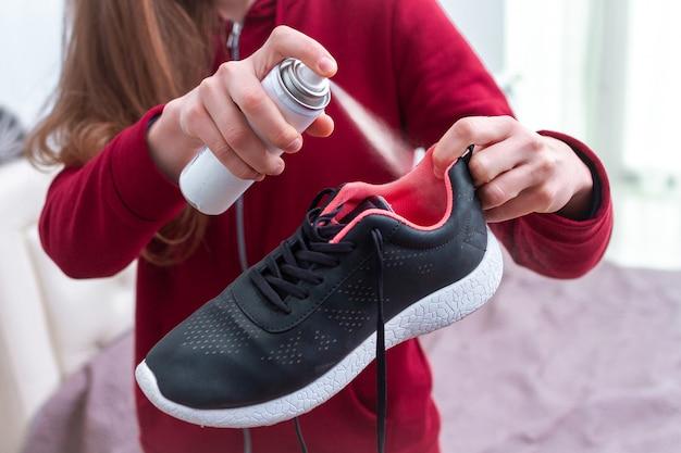Una giovane donna che spruzza deodorante su scarpe da corsa sudate per eliminare l'odore sgradevole e cattivo. le calzature sportive necessitano di pulizia e rimozione degli odori. Foto Premium