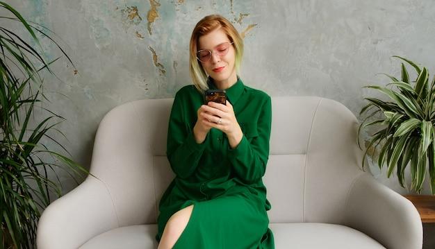Una giovane donna che usa un telefono cellulare, manda un sms e gioca a giochi per cellulare. interni moderni ecologici a soppalco. Foto Premium