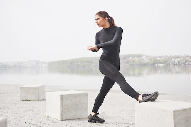 Una giovane donna è impegnata in sport sulla riva di un lago nel parco Foto Gratuite