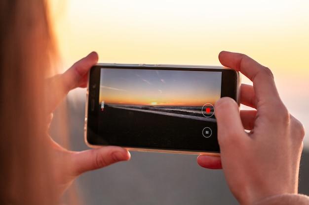 Una giovane donna fotografa il tramonto sulla spiaggia. Foto Premium