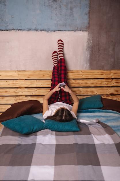Una giovane donna in cuffia e con un telefono cellulare in mano giace sul letto con le gambe alzate. una ragazza si fotografa al telefono. Foto Premium