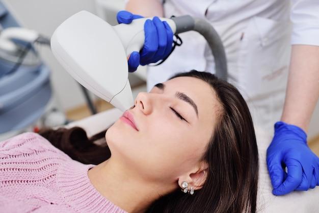 Una giovane donna in una clinica cosmetica Foto Premium
