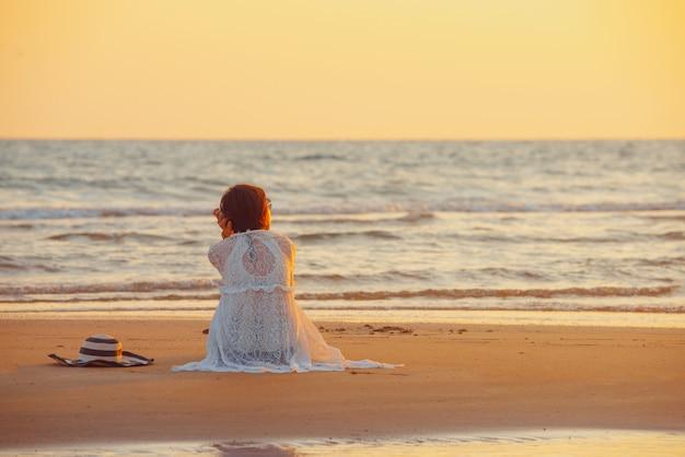 Una giovane donna si trova sulla spiaggia durante un tramonto, le vacanze estive. Foto Premium