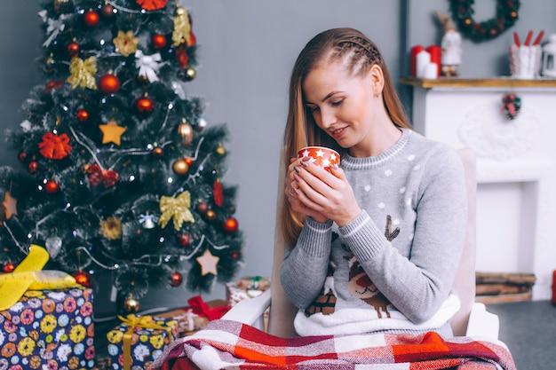 Una giovane donna siede avvolta in una coperta scozzese con una tazza di caffè caldo accanto al camino vicino all'albero di capodanno. Foto Premium