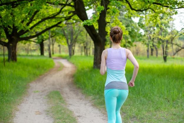 Una giovane donna sportiva in esecuzione in una foresta verde di fine estate. sport e benessere Foto Premium