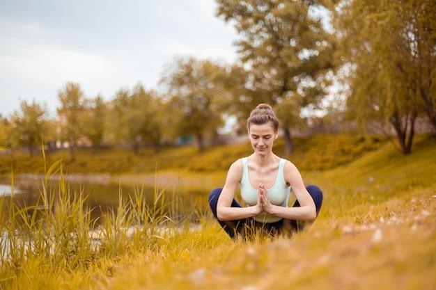 Una giovane donna sportiva pratica yoga su un prato giallo in autunno vicino al fiume, usa yoga assans postura. meditazione e unità con la natura Foto Premium