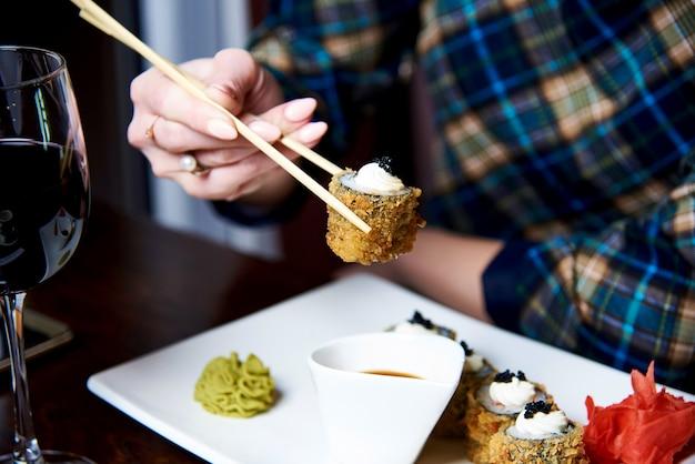 Una giovane donna sta cenando in un ristorante giapponese. Foto Premium