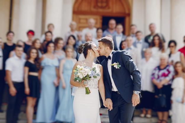Una giovane e bella sposa è in piedi vicino a casa con suo marito Foto Gratuite