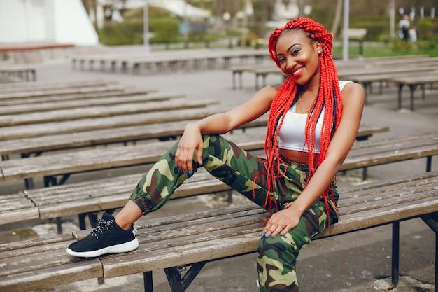 Una giovane ed elegante ragazza dalla pelle scura con il rosso teme seduto nel parco estivo Foto Gratuite