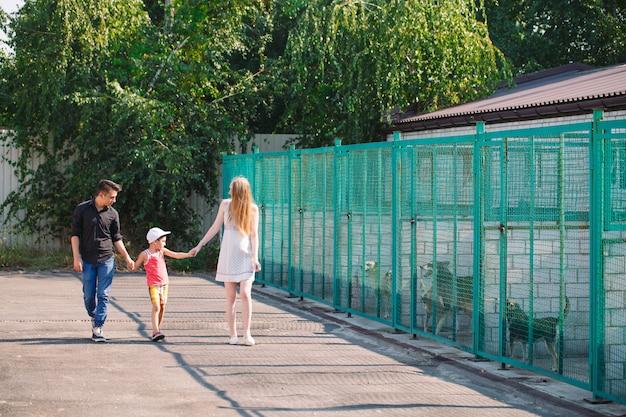 Una giovane famiglia è alla ricerca di un animale domestico in un rifugio per cani. Foto Premium
