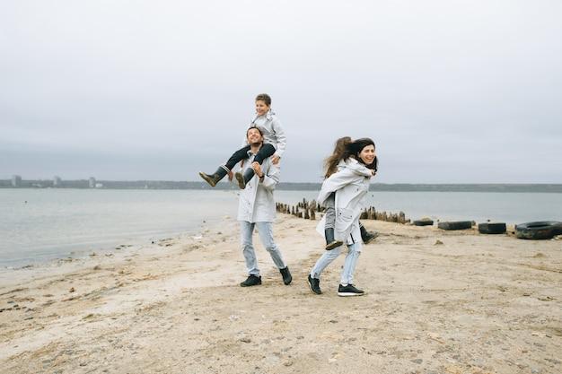Una giovane famiglia si diverte vicino al mare su uno sfondo di barca Foto Premium