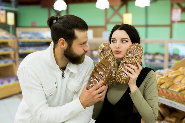 Una giovane famiglia, un uomo e una donna scelgono il pane in un grande supermercato. Foto Premium