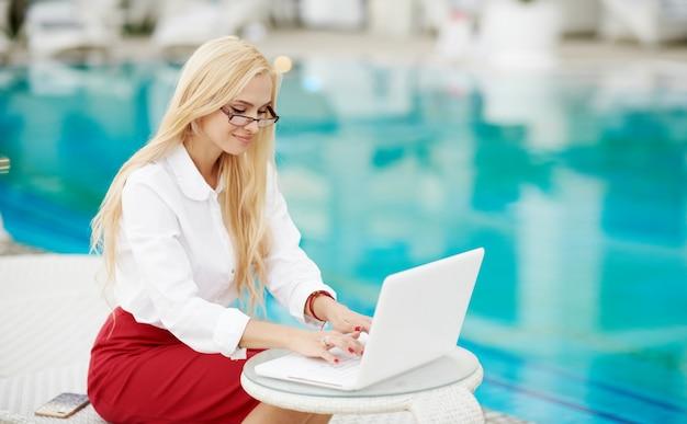 Una giovane imprenditrice che lavora da remoto su un laptop nel suo cortile di casa. Foto Premium