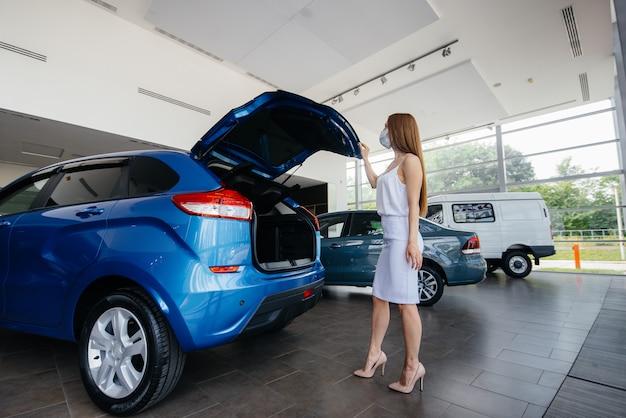 Una giovane ragazza carina ispeziona una nuova auto in una concessionaria di automobili in una maschera durante la pandemia. la vendita e l'acquisto di automobili, nel periodo della pandemia. Foto Premium