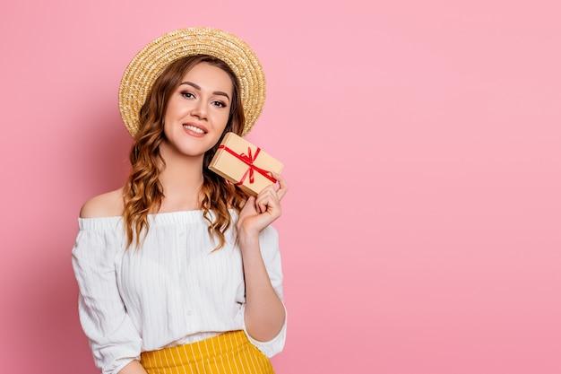 Una giovane ragazza caucasica in un abito bianco di cappello di paglia sorride e tiene una confezione regalo artigianale con un nastro rosso su una parete rosa. la ragazza felice abbraccia una scatola con un regalo Foto Premium