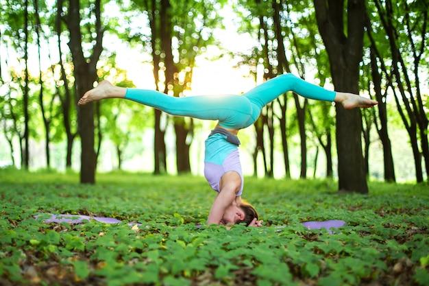 Una giovane ragazza sportiva pratica yoga in una foresta estiva verde chiusa, yoga assans postura. meditazione e unità con la natura Foto Premium