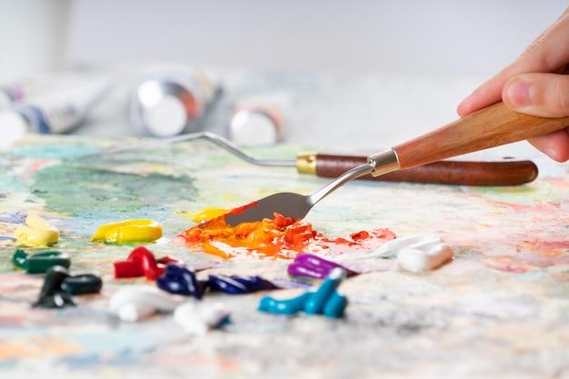 Una giovane ragazza tiene in mano una spatola per disegnare e mescolare colori ad olio. Foto Premium