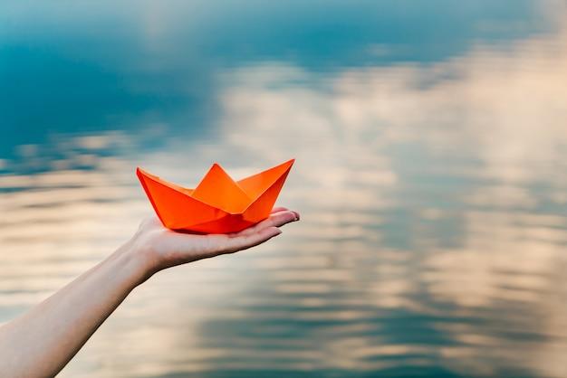 Una giovane ragazza tiene una barca di carta in mano sopra il fiume. l'origami nella forma di una nave ha un colore arancione Foto Premium