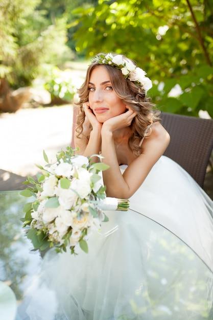 Una giovane sposa si siede a un tavolo di vetro con le mani piegate al mento Foto Premium
