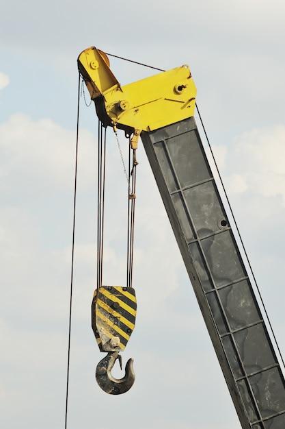 Una gru di costruzione gialla con gancio contro il cielo Foto Premium
