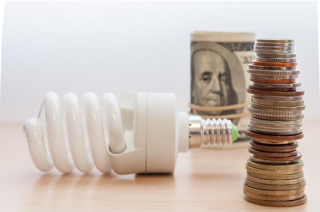 Una lampadina, un'alta pila di monete di diversi paesi e dignità e banconote piegate in un fascio. Foto Premium