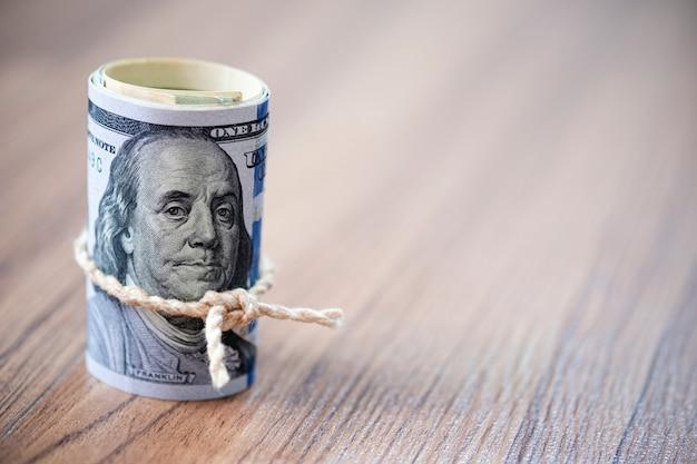 Una macro di un rotolo di 100 banconote del dollaro americano sullo spazio di legno della copia e del fondo Foto Premium