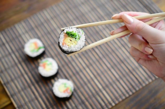 Una mano con le bacchette tiene un rotolo di sushi su una cannuccia di bambù Foto Premium