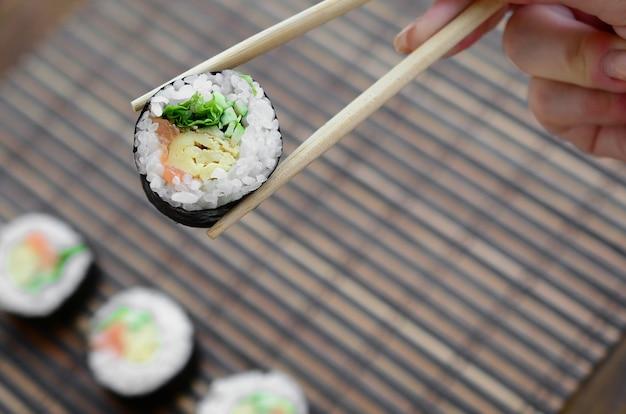 Una mano con le bacchette tiene un rotolo di sushi su una stuoia serwing paglia di bambù Foto Premium