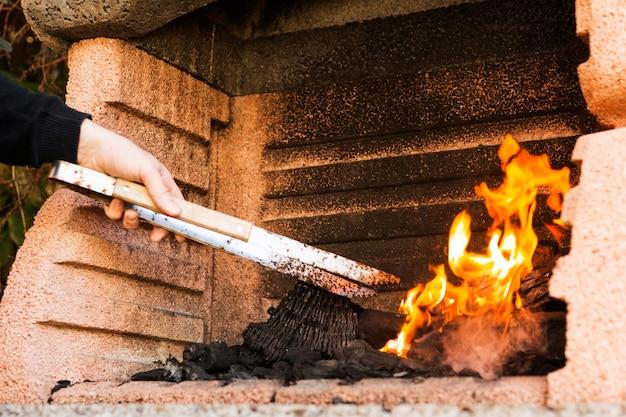 Una mano di persona che brucia carbone con tong in firepit Foto Gratuite