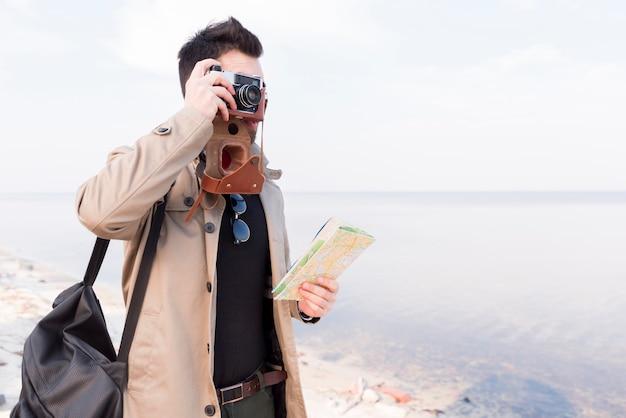 Una mappa della tenuta del viaggiatore maschio a disposizione che prende la foto sulla macchina fotografica alla spiaggia Foto Gratuite