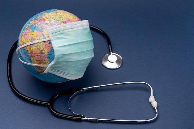 Una maschera medica di coronavirus con uno stetoscopio viene messa sul globo. unione europea. europa. Foto Premium