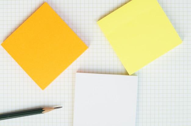 Una matita di legno verde e una carta per appunti appiccicosa su carta griglia bianca. Foto Premium