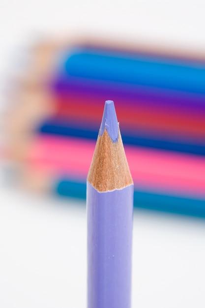Una matita viola su uno sfondo di molti colori Foto Premium