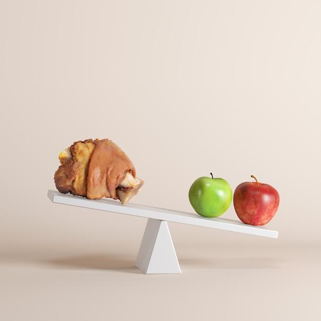 Una mela ribaltamento altalena con gamba di maiale sul lato opposto su sfondo pastello. Foto Premium