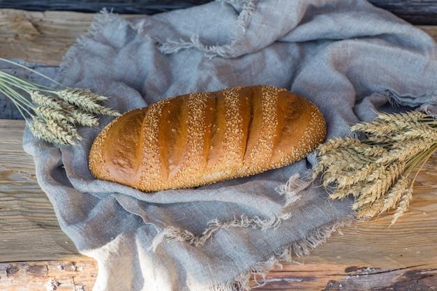Una pagnotta di pane bianco e spighette su un tavolo di legno Foto Premium
