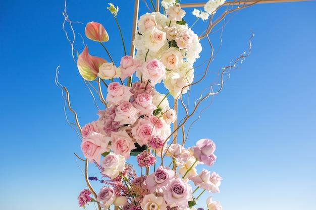 Una parte dell'arco di nozze decorata con fiori freschi è ambientata nel cielo blu Foto Premium