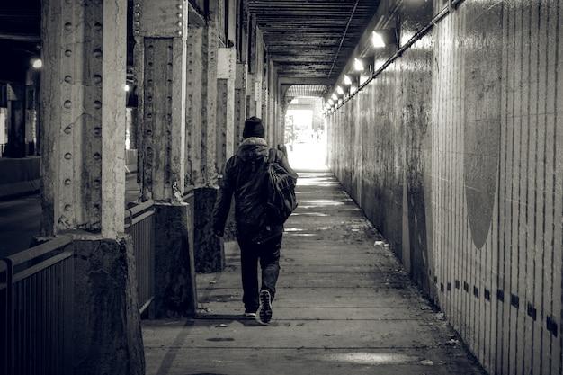 Una persona cammina attraverso un tunnel buio in una grande città, dirigendo la luce. Foto Premium