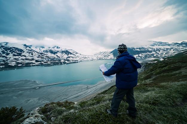 Una persona che guarda la mappa del trekking, il cielo drammatico al crepuscolo, il lago e le montagne innevate, il freddo nordico Foto Premium