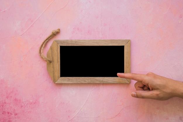 Una persona che punta il dito alla piccola etichetta su sfondo verniciato rosa Foto Gratuite