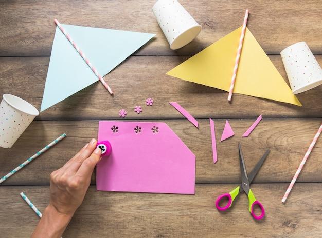 Una persona che punzonatura disegno floreale su carta rosa sopra il tavolo Foto Gratuite