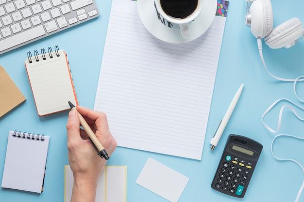 Una persona che scrive sul blocco note con penna sulla scrivania ufficio blu Foto Gratuite