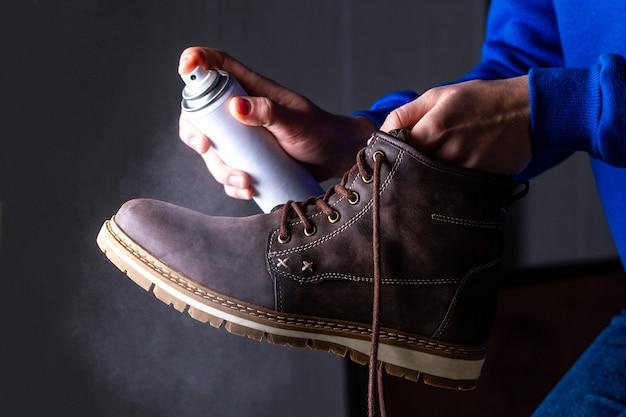 Una persona sta pulendo e spruzzando l'agente sugli stivali casual in pelle scamosciata da uomo per proteggerlo dall'umidità e dallo sporco. lustrascarpe Foto Premium