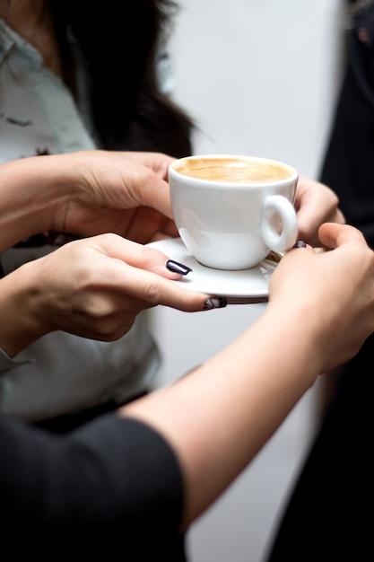 Una persona tiene una tazza di cappuccino Foto Gratuite